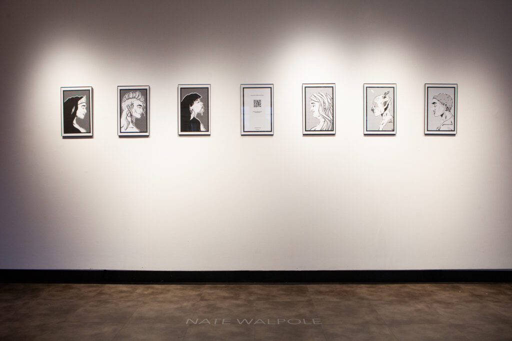 A series of black and white portraits hung on a white wall